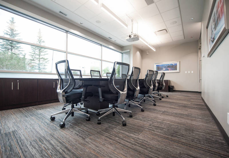 Black chairs and a wood table in carpeted meeting room