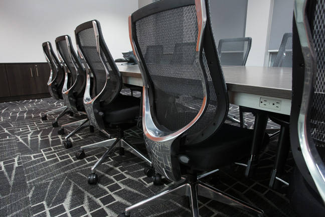 Comfortable black chairs and a wood table in a meeting room with dark carpet