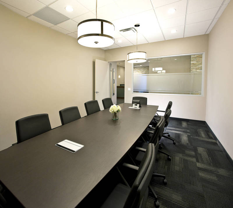 Black chairs and wood table in an office meeting room