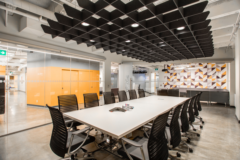 Long white table and black chairs in office conference room